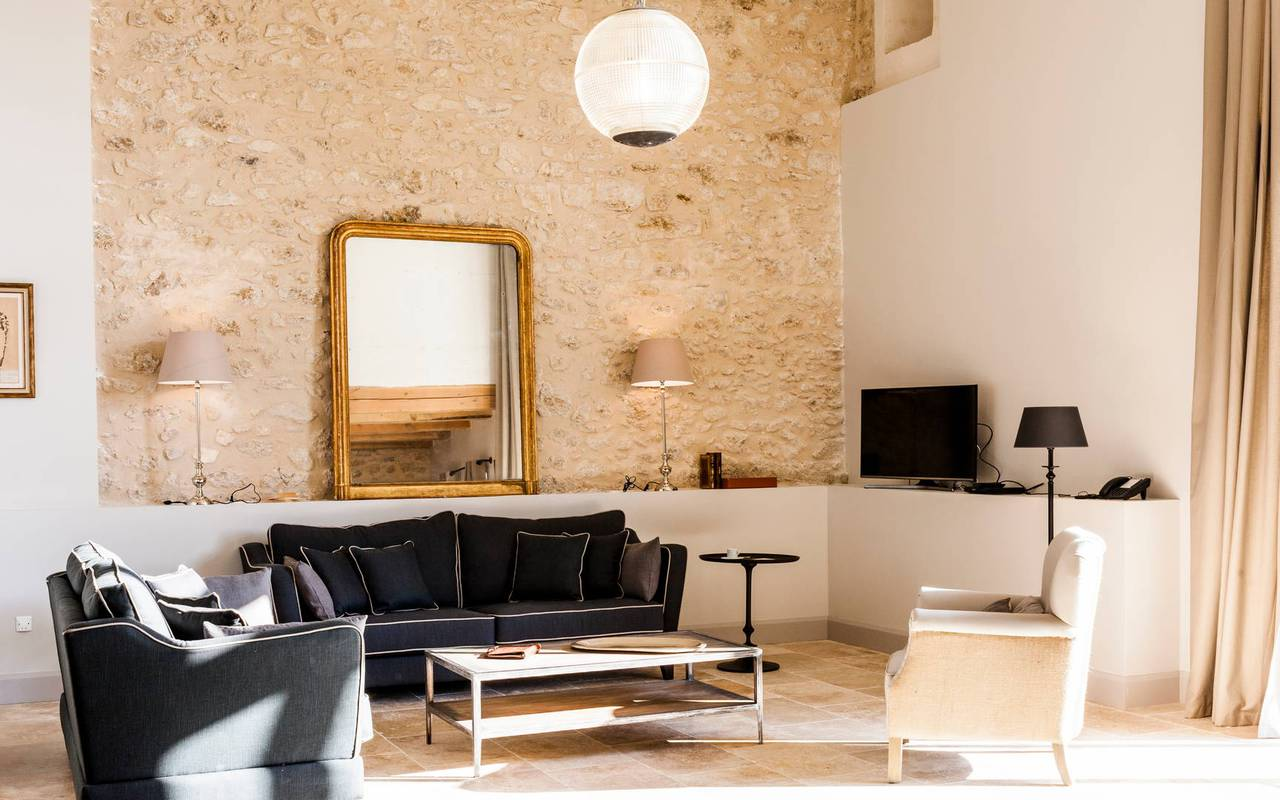 Elegant living room with stone wall in one of our luxury self catering in Languedoc, Château St Pierre de Serjac.