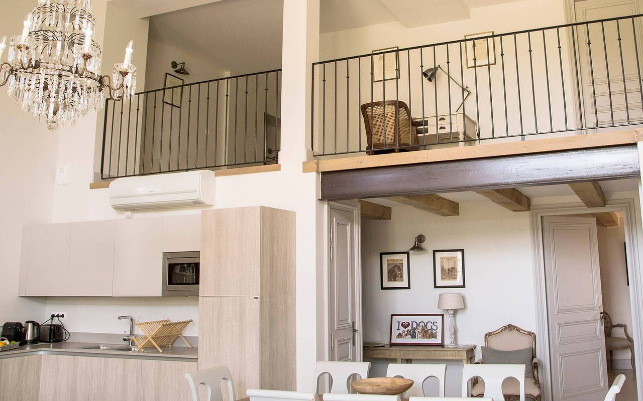 Living room with kitchen and mezzanine in one of our luxury self catering in Languedoc, Château St Pierre de Serjac.