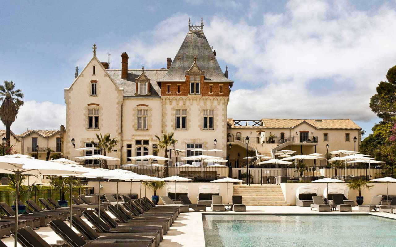 Large pool surrounded by sunbeds in our luxury hotel near Béziers, Château de Serjac