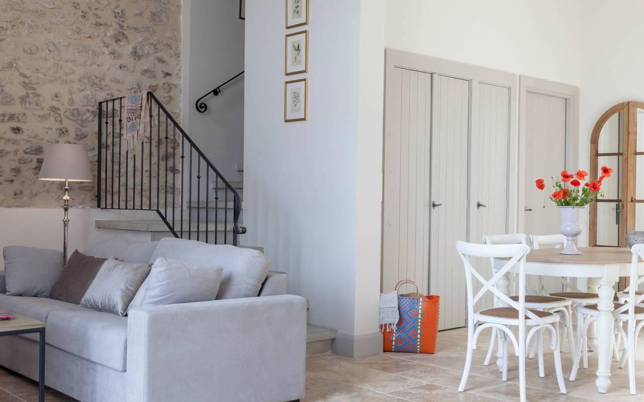 Vue du salon avec mur en pierre de la villa l'Atelier, location de villa près de Béziers, Château St Pierre de Serjac.