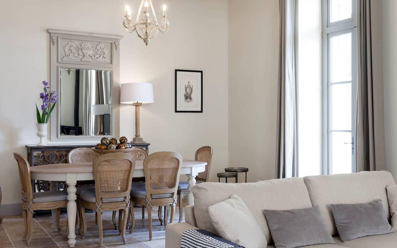 Vue du salon avec canapé et table à manger dans notre location de villa dans l'Hérault, Château de Serjac.