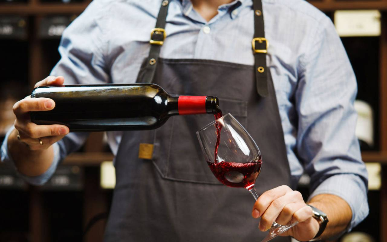 sommelier servant un verre de vin dans notre domaine viticole dans l'Hérault, le Château St Pierre de Serjac.