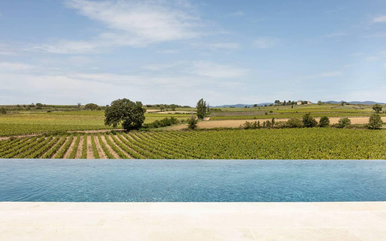 Piscine à débordement avec vue sur les vignes dans nos locations de villa près de Béziers, Château St Pierre de Serjac.