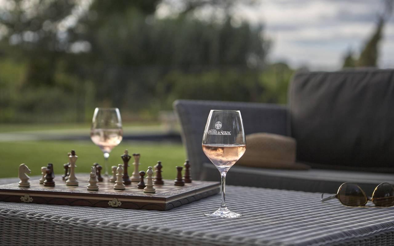 Verres de vin et plateau d'échec dans le jardin du Château de Serjac, pour un séjour insolite dans l'Hérault.