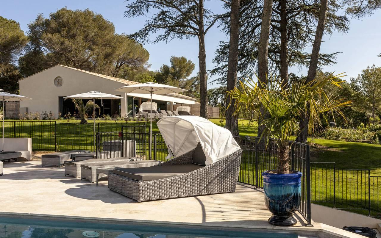 Grands transats au bord de la piscine, location de maison dans l'Hérault, le Château St Pierre de Serjac.
