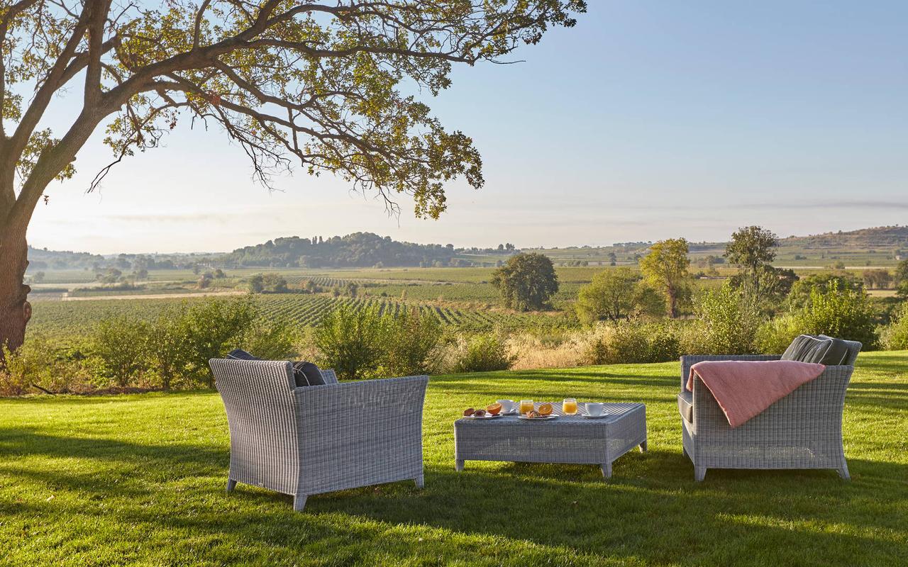 Grand jardin avec salon de jardin, avec vue sur le vignoble, dans domaine viticole dans le sud de la France, Château St Pierre de Serjac.