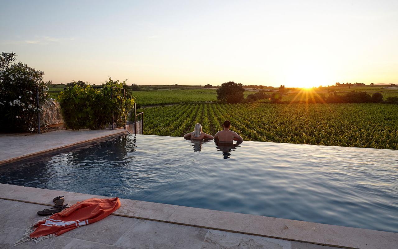 Deux personnes dans une piscine à débordement, surpomblombant les vignes, dans domaine viticole dans le Languedoc Roussillon, Serjac