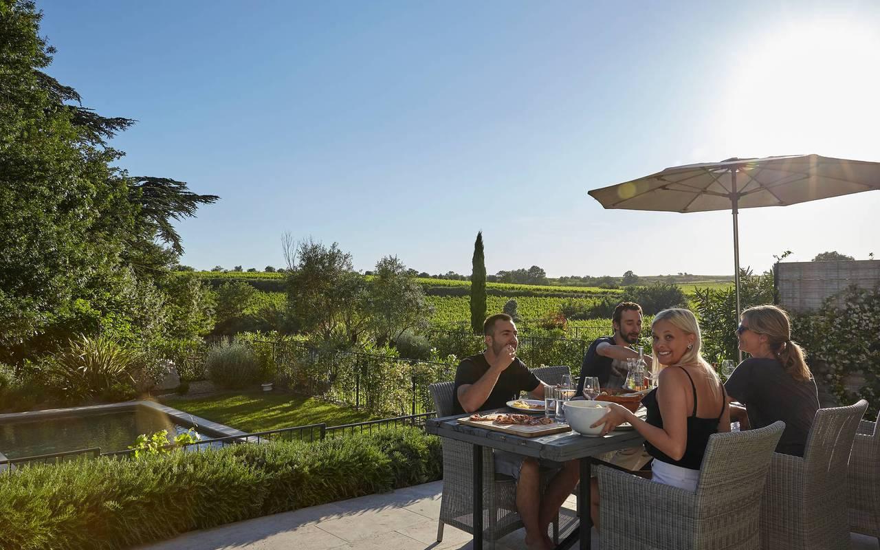 Personnes mangeant dans le jardin de leur villa, restaurant à Puissalicon, Château St Pierre de Serjac.