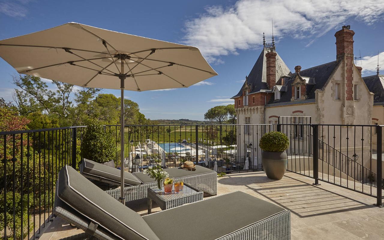 Terrasse avec chaises longues surplombant le domaine, dans notre hôtel de luxe à Pezenas, Château de Serjac.