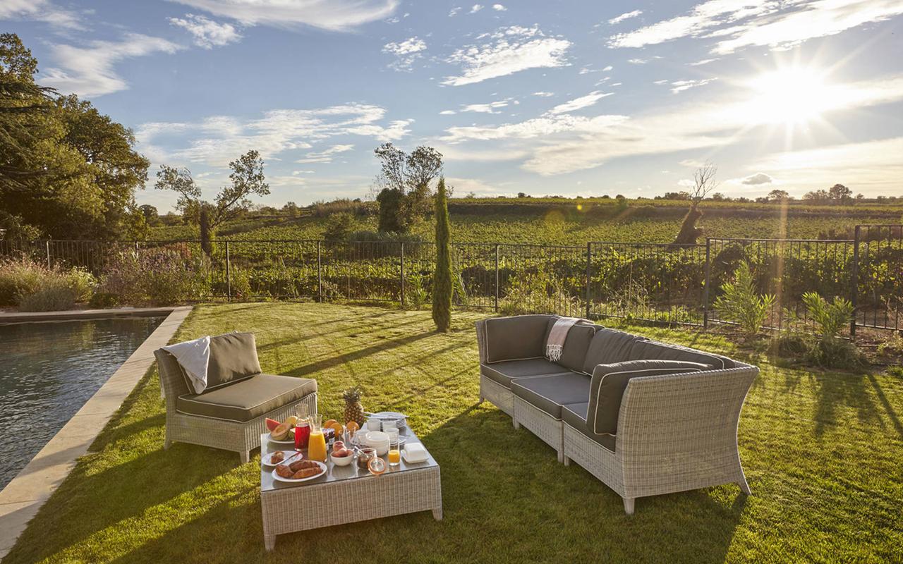 Grand jardin avec fauteuils, au bord de la piscine, dans notre hôtel de luxe près de Pezenas, Château St Pierre de Serjac.