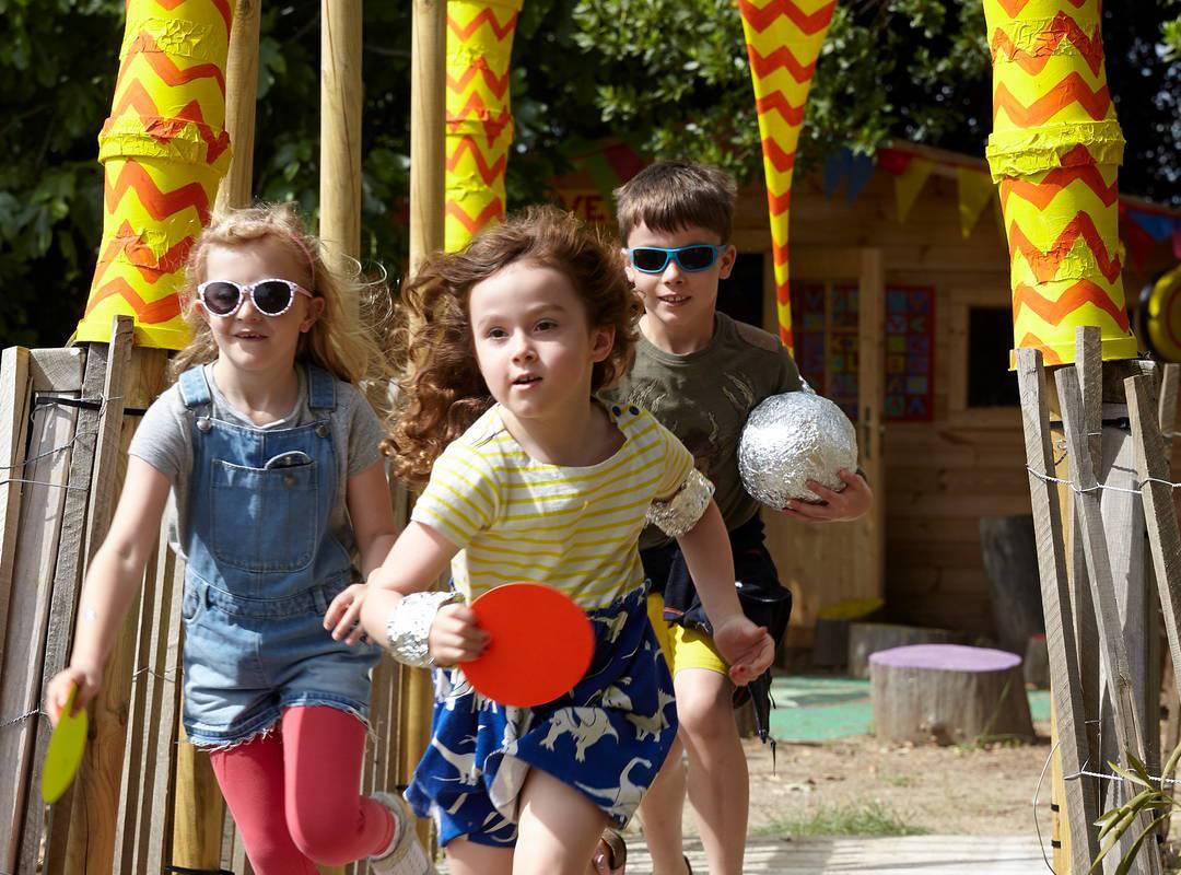 Enfants courant dans le parc, au Château de Serjac pour une nuit insolite en famille en Occitanie.