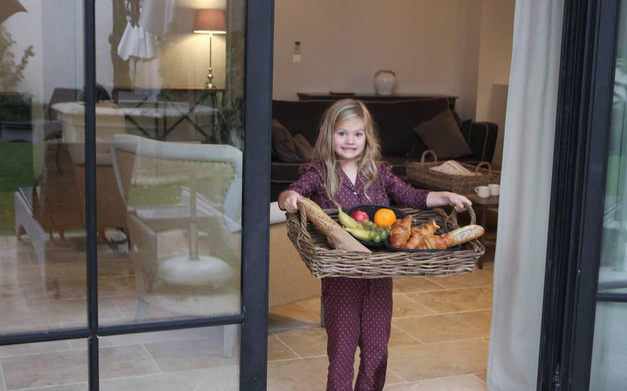 Petite fille portant un plateau de fruits, au Château de Serjac pour une nuit insolite en famille en Occitanie.