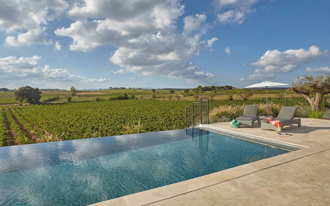 Piscine à débordement donnant sur les vignes, dans notre château hôtel près de Pézenas, le Château de Serjac.