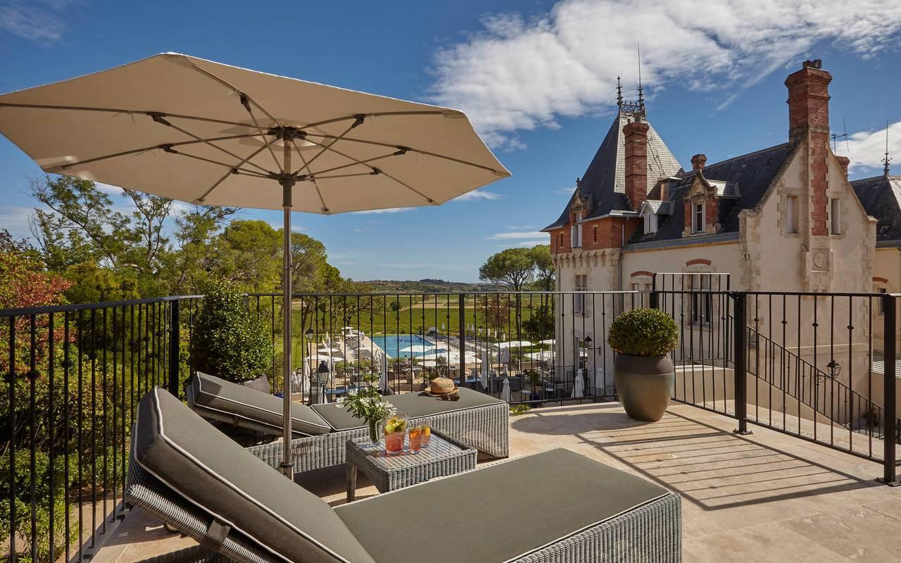 Balcon avec transats avec vue sur parc de notre hôtel près de Pézenas, le Château de Serjac.