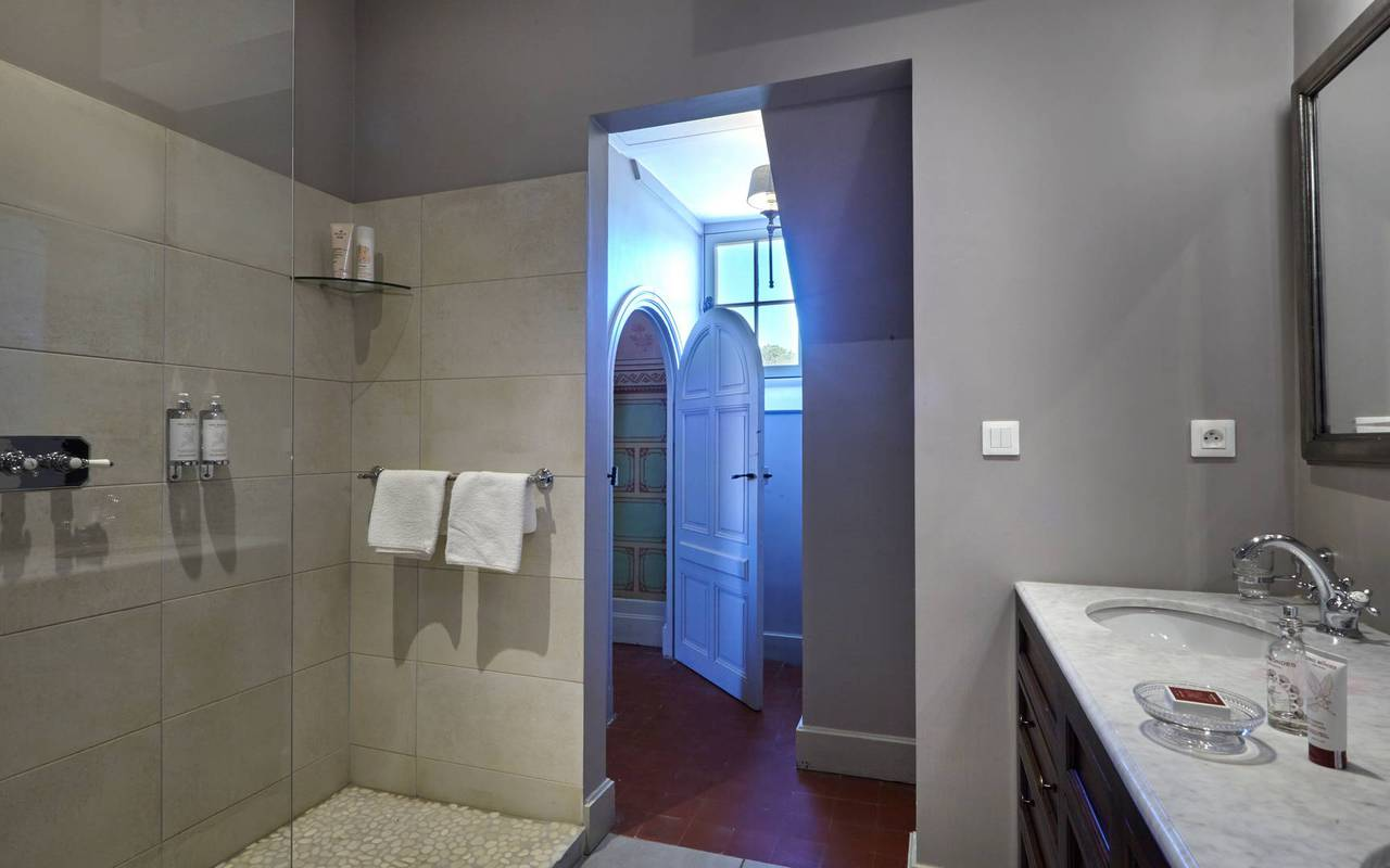 Salle de bain moderne avec douche à l'italienne dans une des chambres de notre hôtel de charme près de Béziers, le Château de Serjac.
