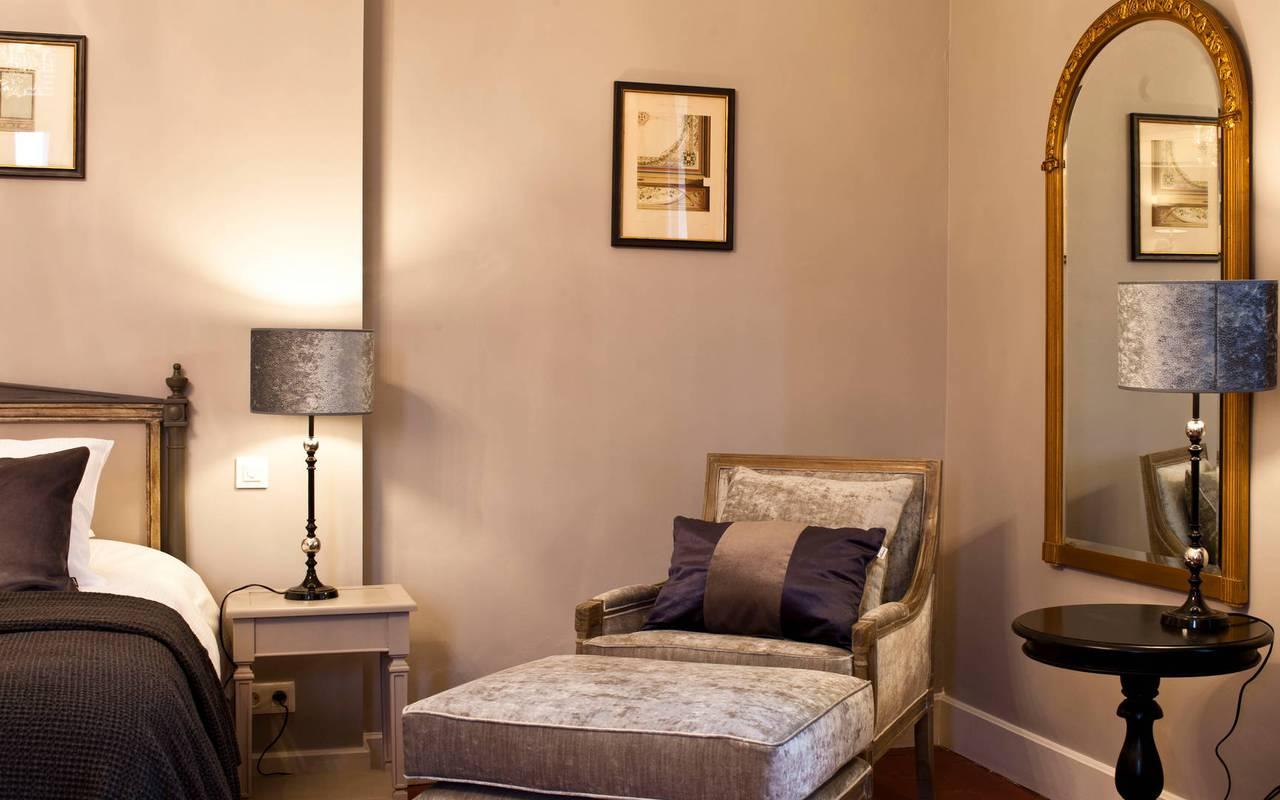 Vue de la chambre luxe avec fauteuil, dans notre hôtel de charme près de Béziers, le Château st Pierre de Serjac.